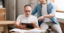 Un Padre y su hijo adulto miran juntos una tablet